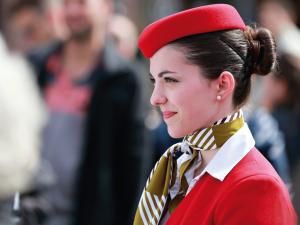Hostess della compagnia aerea volotea, ripresa di proilo con il completo rosso, un foulard a righe gialle e nere